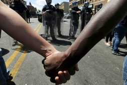 Members of community hold hands in front of police officers in riot gear outside recently looted and burned CVS store in Baltimore